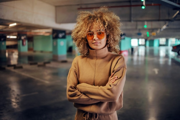 腕を組んで地下駐車場に立ってカメラを見ている巻き毛の女性。
