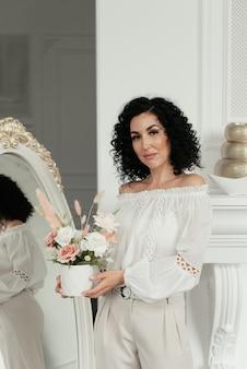 巻き毛の女性は鏡の背景に立っています