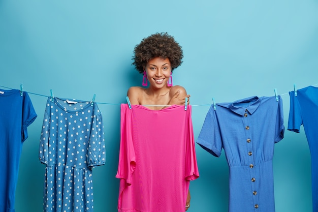 Woman with curly hair stands shy hides naked body behind dress on clothesline smiles gladfully going to get dressed on special event isolated on blue