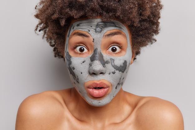 Donna con capelli ricci fissa impressionato applica argilla maschera facciale si prende cura della carnagione secca ansima dalla meraviglia subisce trattamenti di bellezza isolato su bianco
