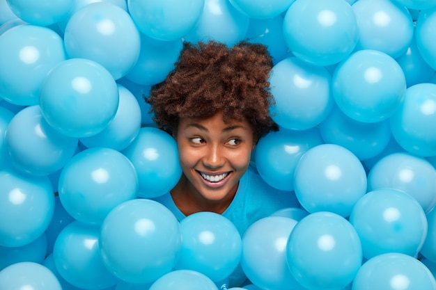 Woman with curly hair sticks out head through inflated blue balloons smiles broadly has happy mood celebrates something.