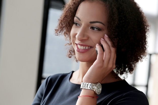 Woman with curly hair talking at the phone