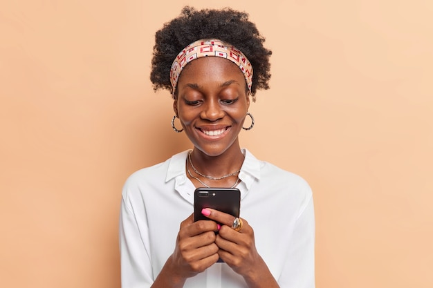 Woman with curly hair uses mobile phone chats online gets message from friend wears headband earrings white shirt isolated on beige