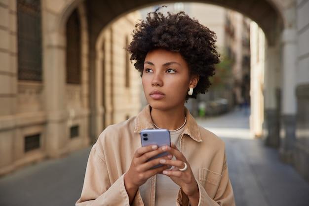 巻き毛の女性は携帯電話を使用してソーシャルネットワークからコンテンツを読み取りますベージュのジャケットを着ています外でポーズをとってインターネットを閲覧しますsmsを送信します
