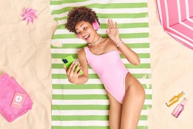 Donna con i capelli ricci onde palmo in gesto di saluto tiene il telefono cellulare verde fa una videochiamata in spiaggia indossa un bikini rosa ascolta musica tramite le cuffie si gode un buon riposo