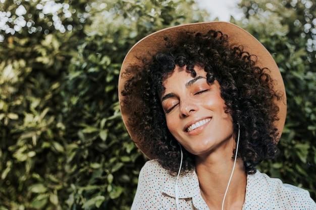 庭のリミックスメディアでイヤホンを身に着けている巻き毛の女性