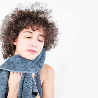 Woman with curly hair wiping her face with towel isolated on white background