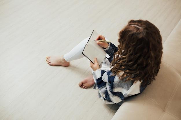 ノートに書き留める巻き毛の女性