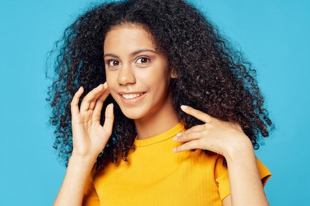 巻き毛の黄色いtシャツスタジオのクローズアップを持つ女性