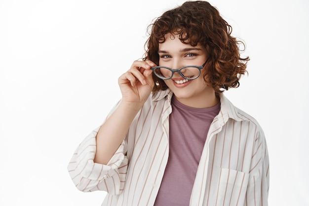 Donna con capelli corti ricci, togliersi gli occhiali e guardando felice la macchina fotografica. ragazza candida con un'espressione del viso allegra, in piedi rilassata su bianco