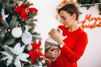 Woman with cute bunny by Christmas tree