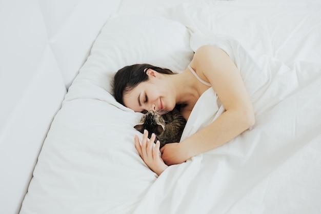 Женщина с милой кошкой, лежа в постели