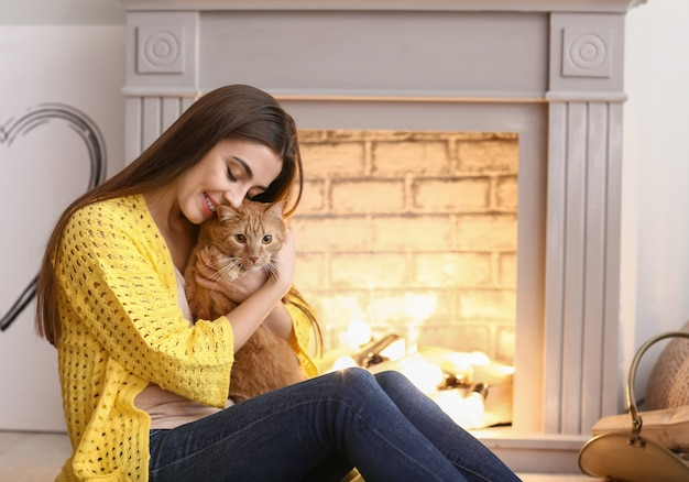 Woman with cute cat resting near fireplace
