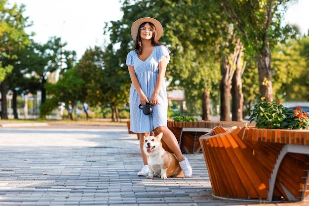 屋外を歩いているかわいいコーギー犬と女性