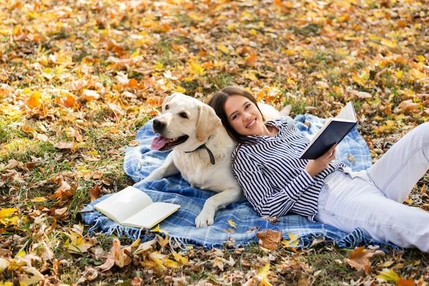 毛布の上に座っているかわいい犬を持つ女性