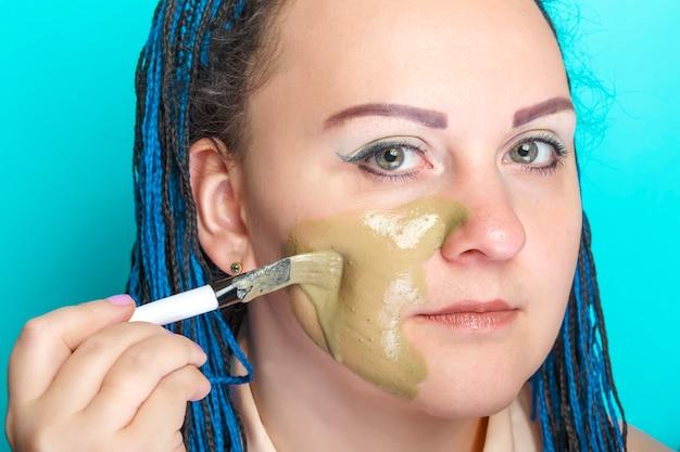 진한 파란색 아프리카 머리띠를 가진 여자는 밝은 파란색 표면에 브러시로 그녀의 얼굴에 녹색 점토 마스크를 적용합니다.