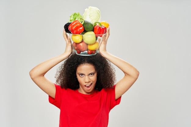 野菜のボウルで暗い巻き毛を持つ女性