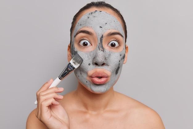 黒い髪の女性が顔に粘土の皮むきマスクを適用しますカメラの訪問で大きな驚きで化粧ブラシの凝視を保持しますスパサロンは灰色の壁にトップレスで立っています