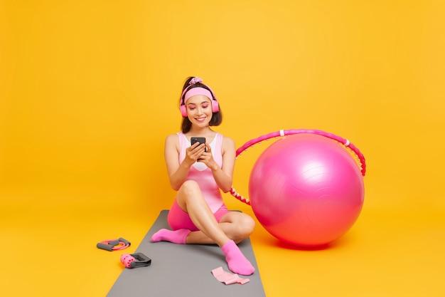 Donna con i capelli scuri controlla i suoi risultati sportivi sull'applicazione per smartphone si siede sul tappetino fitness vestito con abbigliamento sportivo usa palla svizzera hula hoop va per lo sport pone al coperto