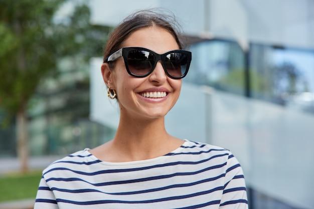 Женщина с холодными темными волосами в прекрасный весенний день носит солнцезащитные очки в полосатом джемпере позирует на размытом