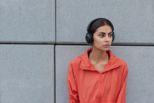 Woman with dark hair dressed in casual anorak looks away thoughtfully listens music via wireless headphones poses against grey wall outdoor blank space for your information