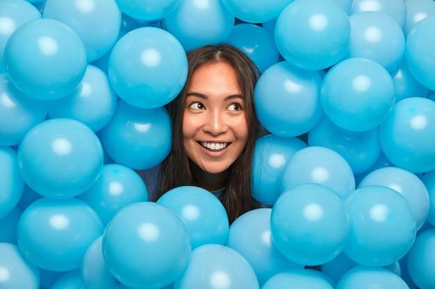 Женщина с темными волосами наслаждается празднованием праздника, задумчиво смотрит в сторону в окружении множества надутых синих воздушных шаров