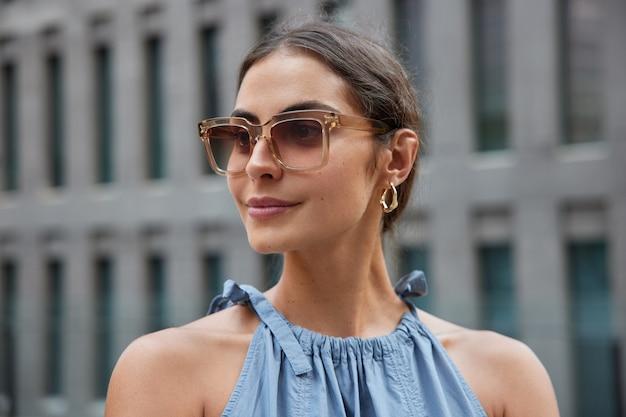 Donna con i capelli scuri concentrata via con espressione soddisfatta indossa occhiali da sole alla moda e vestito cammina per la città discon qualcosa di nuovo posa su sfocato