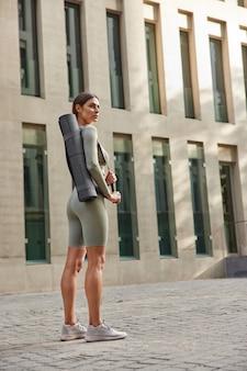 Женщина с темными волосами в спортивной одежде расслабляется после тренировки на свежем воздухе в летний день несет свернутые стенды каремата возле современного здания