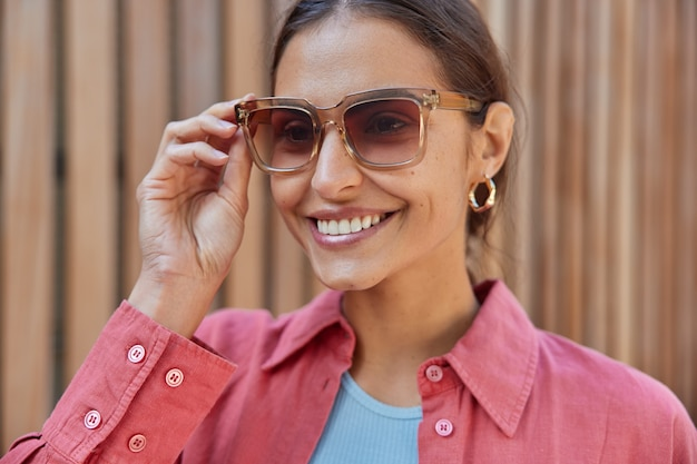 Woman with dark hair keeps hand on sunglasses dressed in pink shirt concentrated into distance feels happy enjoys sunny day and recreation time. women and style