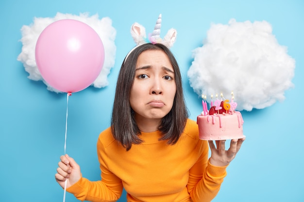 Woman with dark hair looks sadly at camera celebrates birthday alone holds delicious cake and inflated balloon isolated on blue