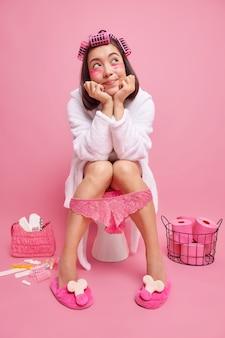 Женщина с темными волосами делает прическу роликами, накладывает косметические подушечки под глаза, чувствует себя расслабленной, сидя на унитазе, носит белый халат, кружевные трусики на ногах, позирует в ванной