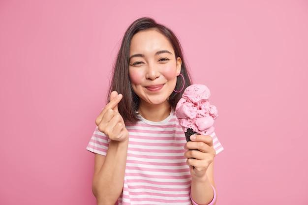검은 머리를 가진 여성이 미니 하트 제스처를 만들어 맛있는 아이스크림 제스처를 먹습니다. 기호처럼 한국어가 사랑의 포즈를 표현합니다.
