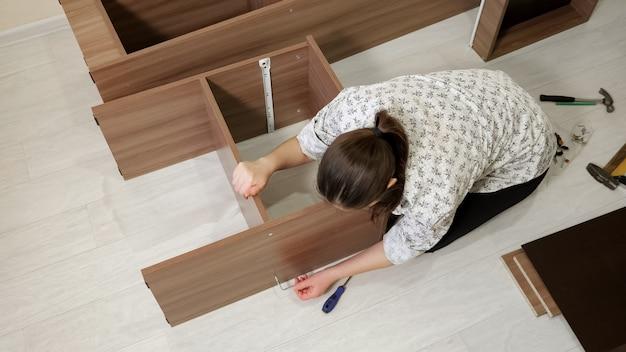 黒髪の女性が床に座って、棚の部品を接続するための新しい既製のキャビネット回転ツールを組み立てます上面図
