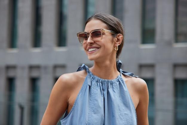 검은 머리를 한 여성이 활짝 웃고 선글라스를 끼고 파란 드레스를 입고 도시 환경에서 여름 산책을 즐깁니다. 밖에서 친구를 만나서 반가워요.