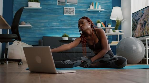 ノートパソコンでオンラインフィットネススポーツビデオを見ながら、ヨガマップで体の筋肉を伸ばしているリビングルームでピラティストレーニングをしている暗い肌の女性。健康的なライフスタイルを楽しむ柔軟な大人