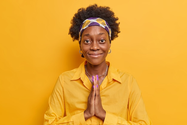 Женщина с темной кожей, сложив ладони вместе, просит об одолжении улыбается, нежно носит рубашку и повязку на голове, изолированную на желтом ярком