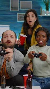 ジョイスティックを使用してゲームの競争のために遊んでいる間、友人の男性に対してビデオゲームを失う暗い肌の女性