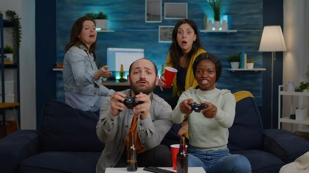ゲームの競争のために遊んでいる間、友人の男性に対してビデオゲームを失う暗い肌の女性