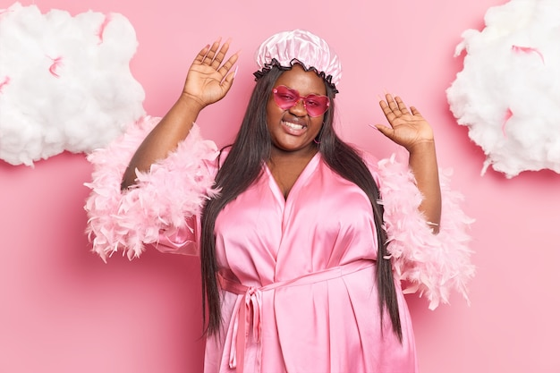Woman with dark skin smiles pleasantly raises arms dances carefree wears bath hat dressing gown and sunglasses isolated on pink