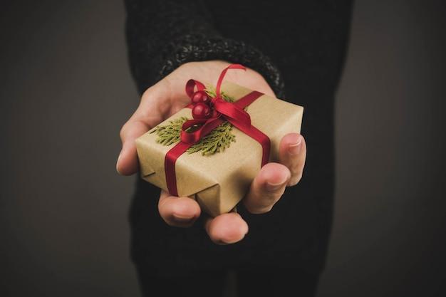 Женщина с темным свитером, держа маленький рождественский подарок. черный фон.
