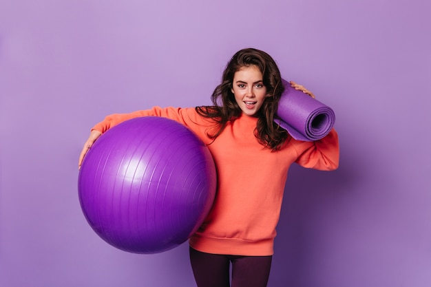 Woman with dark voluminous hair dressed in orange sweatshirt keeps fitball and fitness mat on purple wall