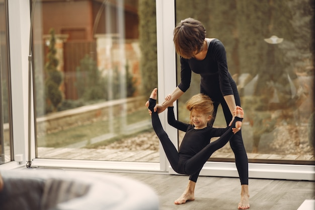 Woman with daughter is engaged in gymnastics