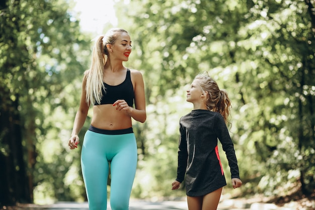 Woman with daughter jogging in park
