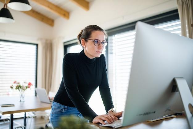 ホームオフィス、コロナウイルスと検疫の概念で屋内で働く娘を持つ女性。
