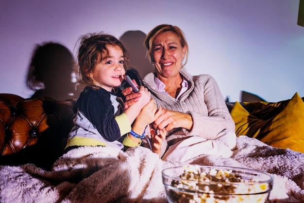 Woman withdaughters watching tv in dark