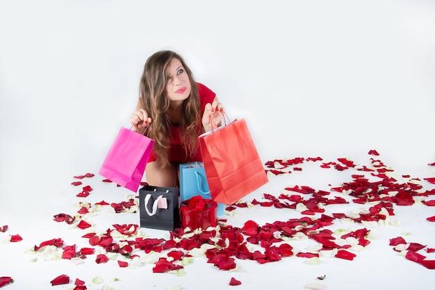 Женщина с восторгом прижимается к бумажным пакетам с покупками среди лепестков роз на