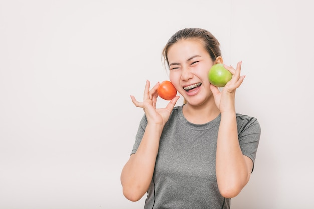 Woman with detal braces having fun with green apple and tomato