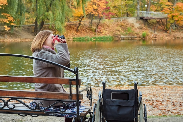 Woman with disabilities sitting on a bench taking pictures in an autumn day