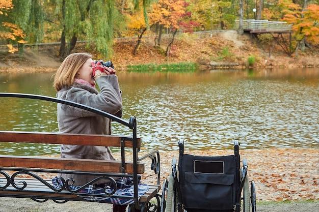 Женщина с ограниченными возможностями сидит на скамейке и фотографирует в осенний день