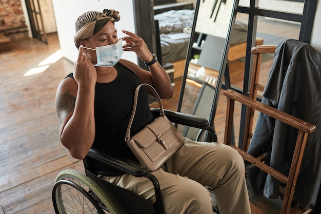 Woman with disability putting on mask